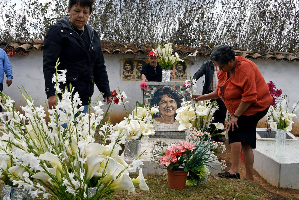Relatives and friends place flowers at indigenous environmentalist Berta Caceres grave in La Esperanza, Honduras, on March 3, 2018.  Relatives and indigenous people demanded justice to the intellectual authors of the murder of the prestigious environmentalist Berta Caceres, executed two years ago for opposing the construction of a hydroelectric dam on a river. / AFP PHOTO / Orlando SIERRA        (Photo credit should read ORLANDO SIERRA/AFP via Getty Images)