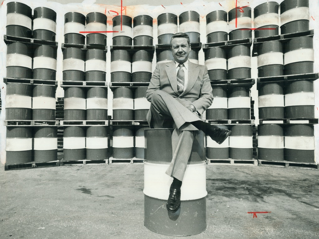 CANADA - APRIL 20:  Every Canadian man, woman and child consumes on average each year the energy equivalent of these 49 barrels of crude oil. Affluent Canadians eat up more energy per capita than Americans. That much oil dwarfs John Armstrong (above), chairman of Imperial Oil, who perches on one barrel with 48 more arrayed behind him. Even at low Canadian prices, before refining, this quantity costs about $440.   (Photo by Harold Barkley/Toronto Star via Getty Images)