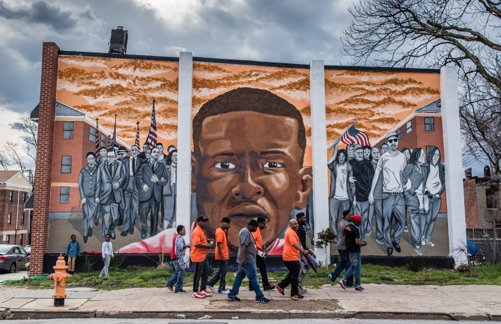 Safe Streets workers walk past a mural of Freddie Gray, painted by the artist Nether, in Sandtown-Winchester in West Baltimore in 2016.