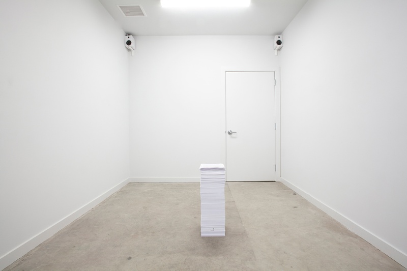 In the center of a room with white walls and a grey floor is a four foot tall stack of papers, consisting of medical bills and a life-care plan. In two corners of the room are speakers that play instrumental hold-tone music.