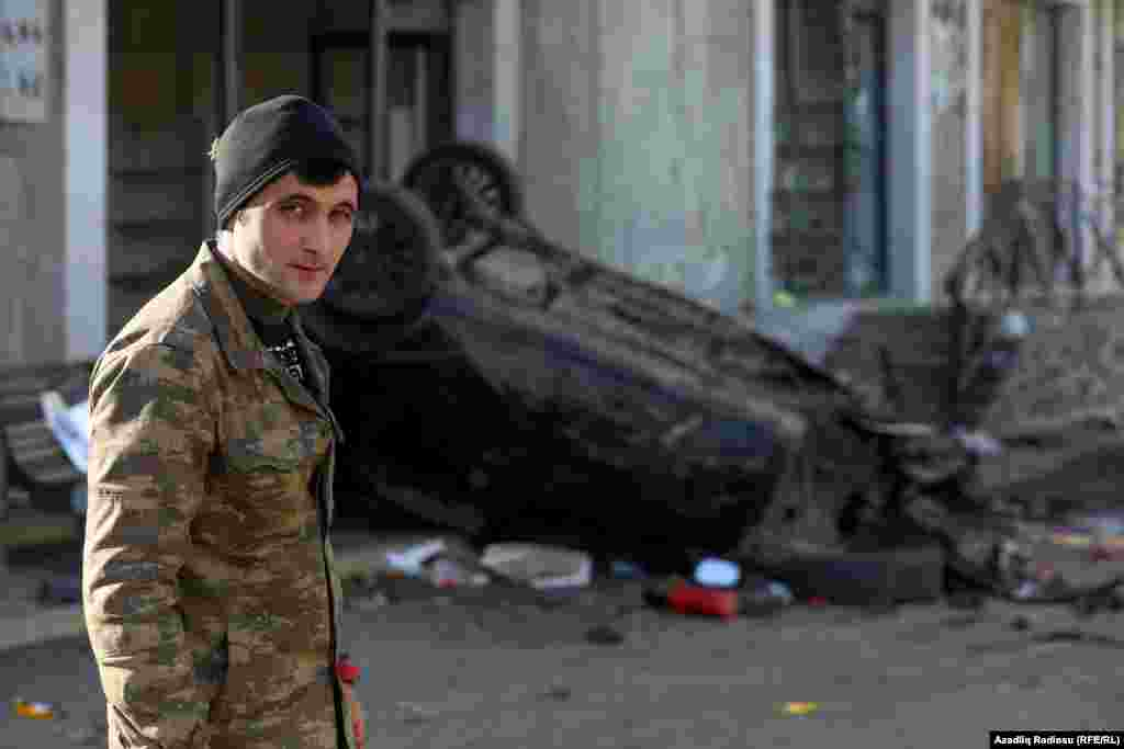An Azerbaijani soldier poses in front of a damaged car in Hadrut.
