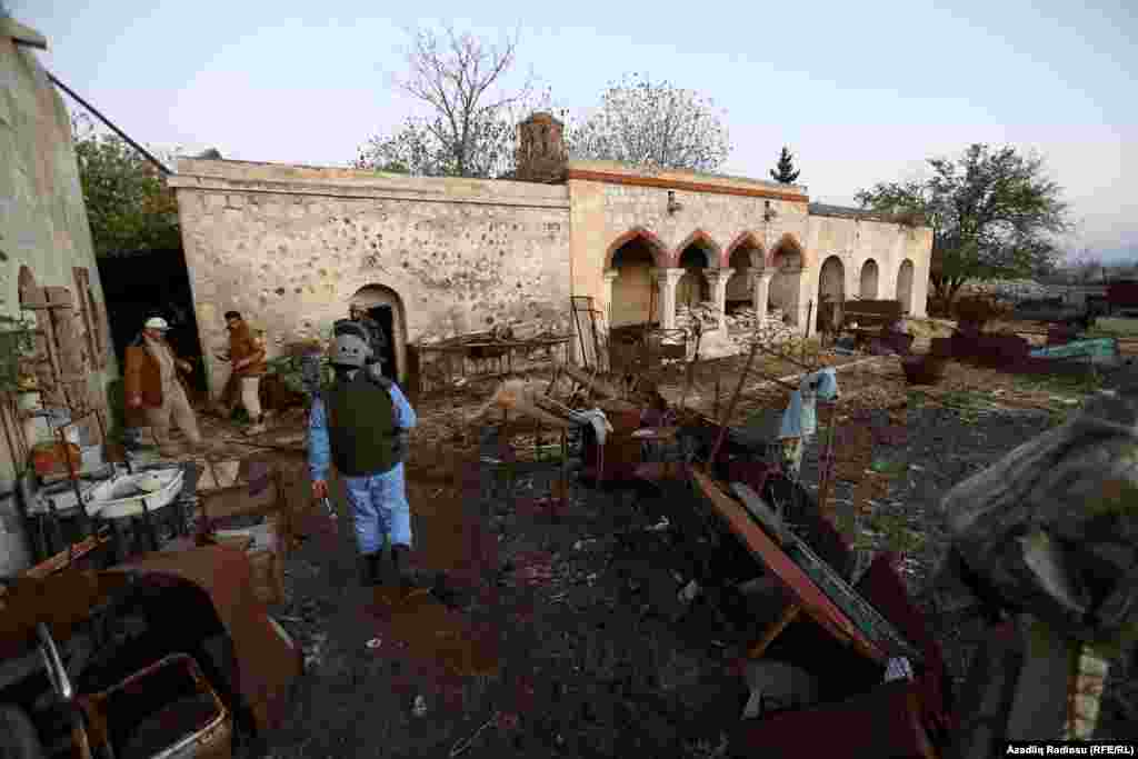 An Azerbaijani soldier carries out demining work amid damaged historical buildings in Agdam.