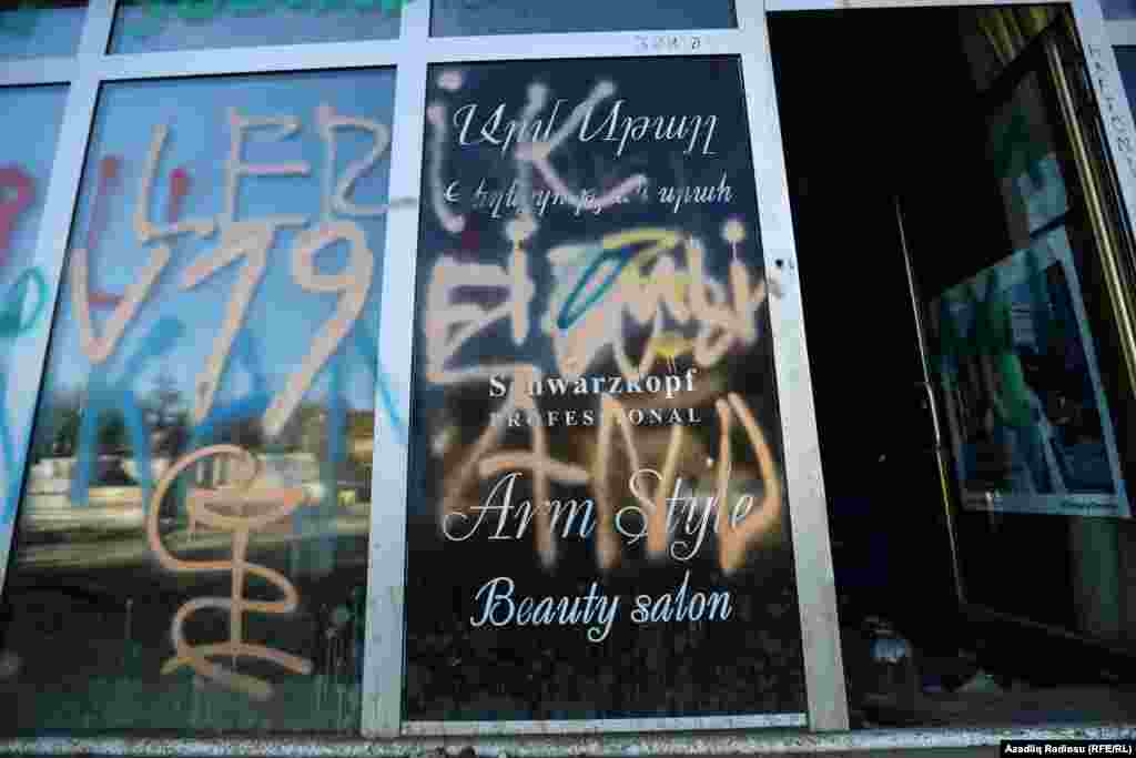 A Hadrut shop window covered in graffiti.