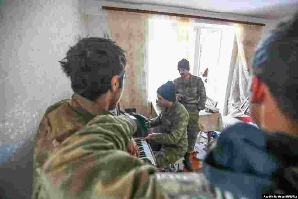 An Azerbaijani soldier plays the piano, watched by his comrades, in an abandoned house in Hadrut.