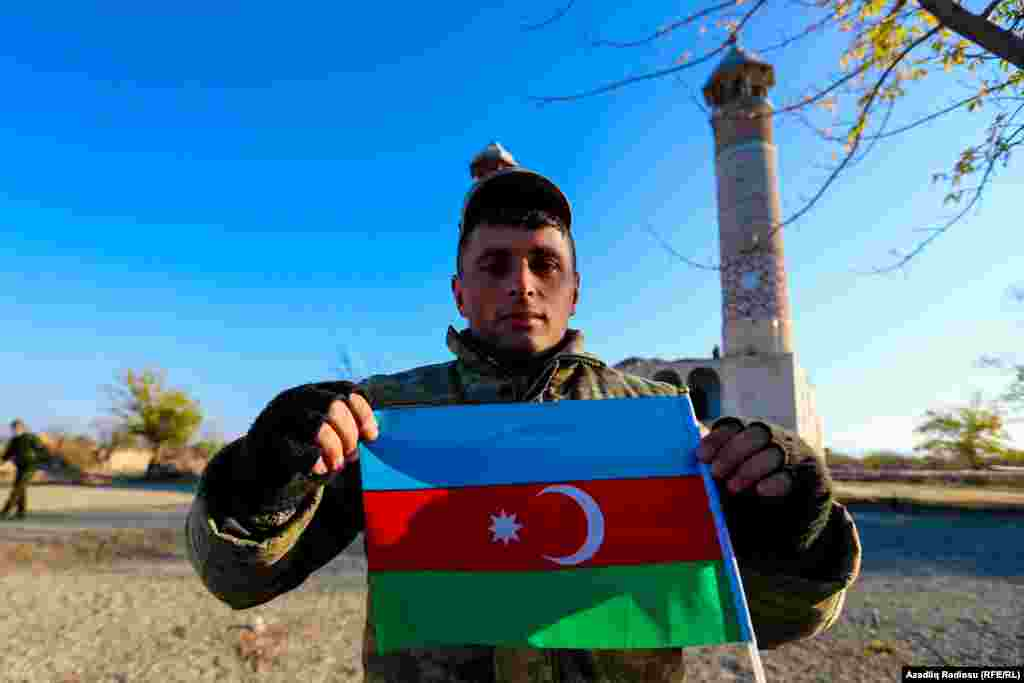 An Azerbaijani poses with his country's flag in front of Agdam mosque on November 24.