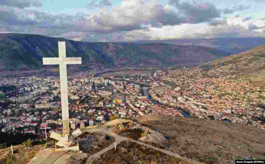 A viewpoint above Mostar dominated by a 33-meter high cross. Since the end of the conflict in 1994, Mostar has been divided with Croats mostly living on the west side of the Neretva River (left side of photo) and Bosniaks to the east.