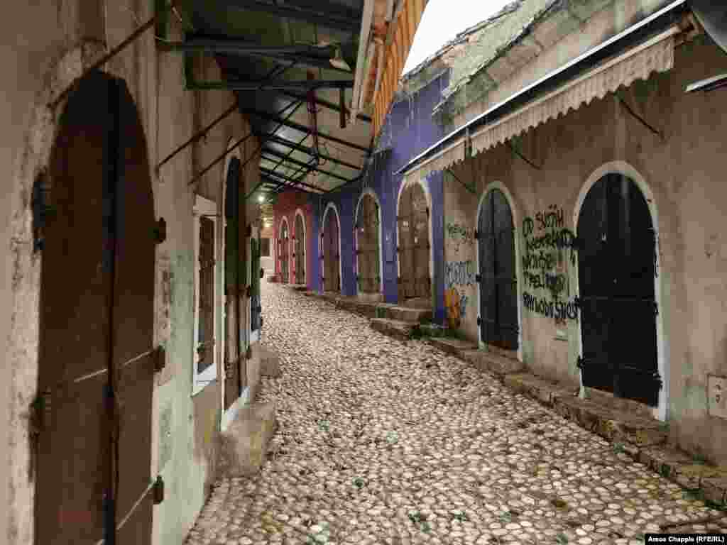 """Shuttered stalls next to Mostar's old bridge in the early afternoon. The graffiti says """"Of all my quirks, I most despise indifference.""""  Bosnia's new government will also be tasked with the fixing the enormous damage done to Mostar's once bustling tourist trade as a result of the COVID pandemic."""