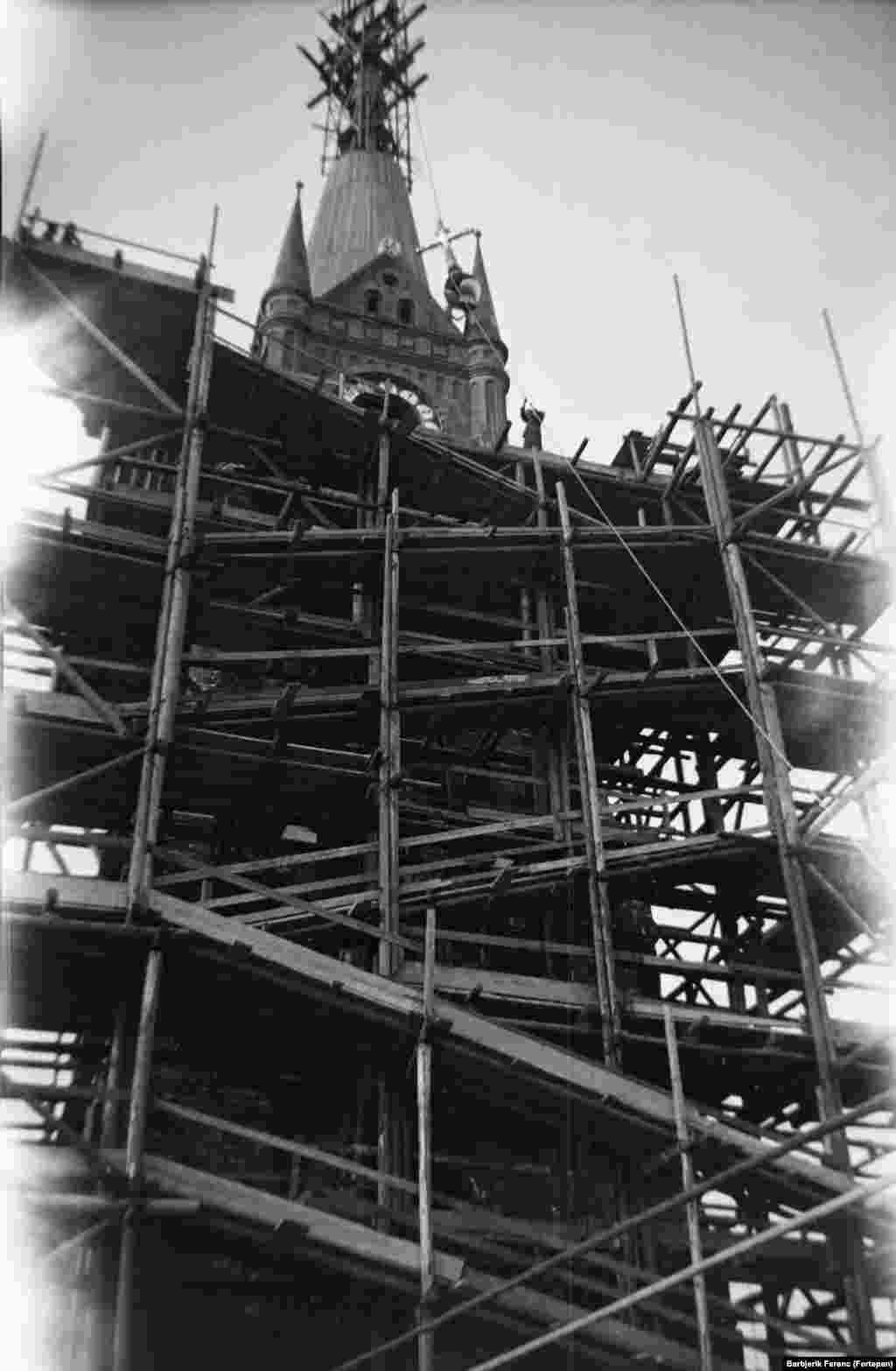 1937: A cross being raised onto the spire of the Church of the Holy Spirit as it nears completion.