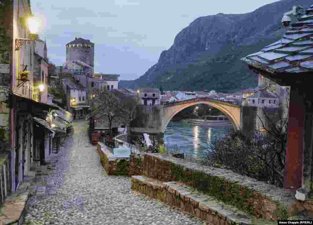 """An empty tourist area next to Mostar's famous bridge.  Enisa Basic, who runs a historic cafe next to the bridge, told RFE/RL her business employed 10 staff last year when it was thriving. She says the lack of tourism due to the pandemic has forced her to fire all of them. She is cautiously optimistic that the winners of the upcoming elections will help businesses like hers survive: """"This is a very good city, but the people who have run it just put the money in their own pockets. They don't care about regular people like me. After the elections, we hope things will change for the better."""""""