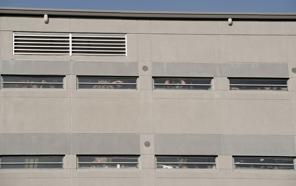 Inmates at the Etowah County Detention Center crowd to the windows to watch as protesters march in front of the detention center to protest Alabama House Bill 56 and the U.S. Immigration and Customs Enforcement program Saturday, Dec. 3, 2011 in downtown Gadsden, Ala. Members of Occupy Birmingham organized the protest. (AP Photo/The Gadsden Times, Sarah Dudik)