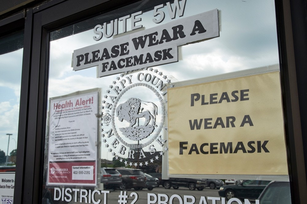 Signs encourage the wearing of face masks Thursday, June 18, 2020, at a Sarpy County office in Papillion, Neb., where face covering is recommended but not mandatory. The Omaha World-Herald reports that Republican Gov. Pete Ricketts has told local officials they would not receive any of the $100 million allotted to Nebraska in an economic rescue law if they require the public to wear masks in courthouses and other government buildings. (AP Photo/Nati Harnik)