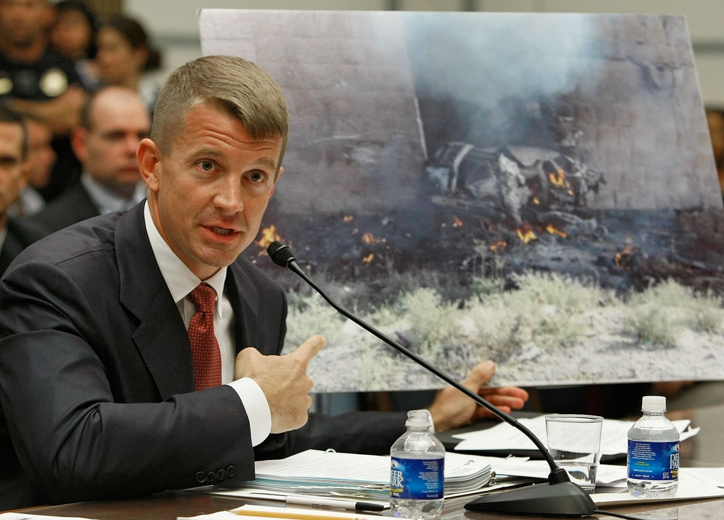 Erik Prince, chairman of the Prince Group, LLC and Blackwater USA, holds up a picture showing the affect of a car bomb while testifying during a House Oversight and Government Reform Committee hearing on Capitol Hill October 2, 2007 in Washington DC.