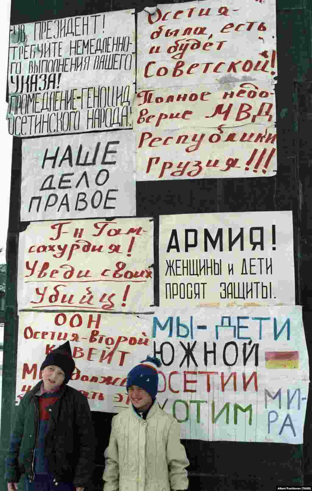 """Children in Tskhinvali on January 1, 1991, pose with banners that include the declaration: """"Ossetia was, is, and always will be Soviet!""""  Many Georgians saw ethnic Ossetians as a traitorous fifth column while their country battled for freedom from the Soviet Union. Meanwhile, Ossetians felt sidelined by new laws that made Georgian the only official language of the country and obstructed Ossetian political representation in Tbilisi."""