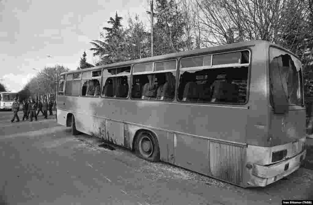 """A burnt-out bus in Tskhinvali after a convoy of vehicles filled with ethnic Georgians attempted to enter the city in November 1990.  After South Ossetia declared further autonomy from Tbilisi, Gamsakhurdia urged """"all Georgians capable of bearing arms [to] join the march against Tskhinvali! The storming is to start on the morning of November 23!"""" A convoy of thousands of Georgian men was met with roadblocks and crowds of Ossetians. In the clashes that followed at least six people were killed."""