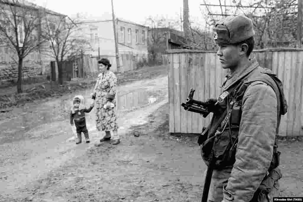 """A Soviet soldier stands guard in Tskhinvali in December 1990.  Moscow sent a contingent of Interior Ministry troops to South Ossetia to """"prevent clashes and bloodshed,"""" but Tbilisi protested the Soviet """"meddling"""" and sent in their own fighters."""