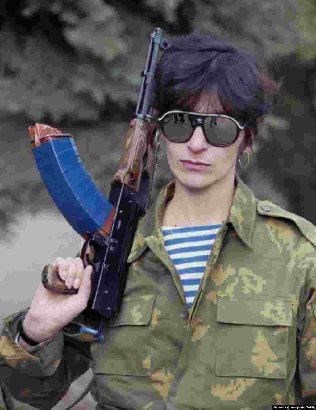 """A female Ossetian fighter poses for a portrait.  A Russian woman married to a Georgian told Human Rights Watch she attempted to find help after the couple's house was robbed but was told """"you [cooked] this porridge, now eat it!"""""""