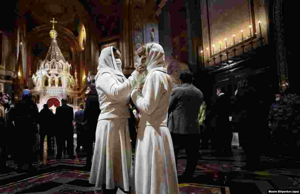 Russian Orthodox devotees adjust their face masks inside Christ the Savior Cathedral in Moscow.