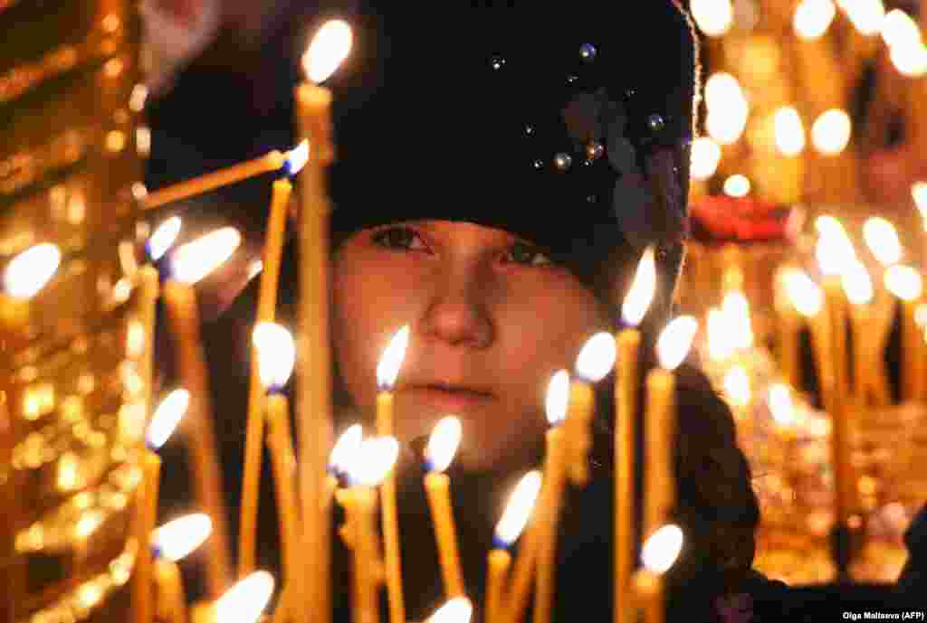 A girl lights a candle during a Christmas service in the Kazan Cathedral in St. Petersburg, Russia.
