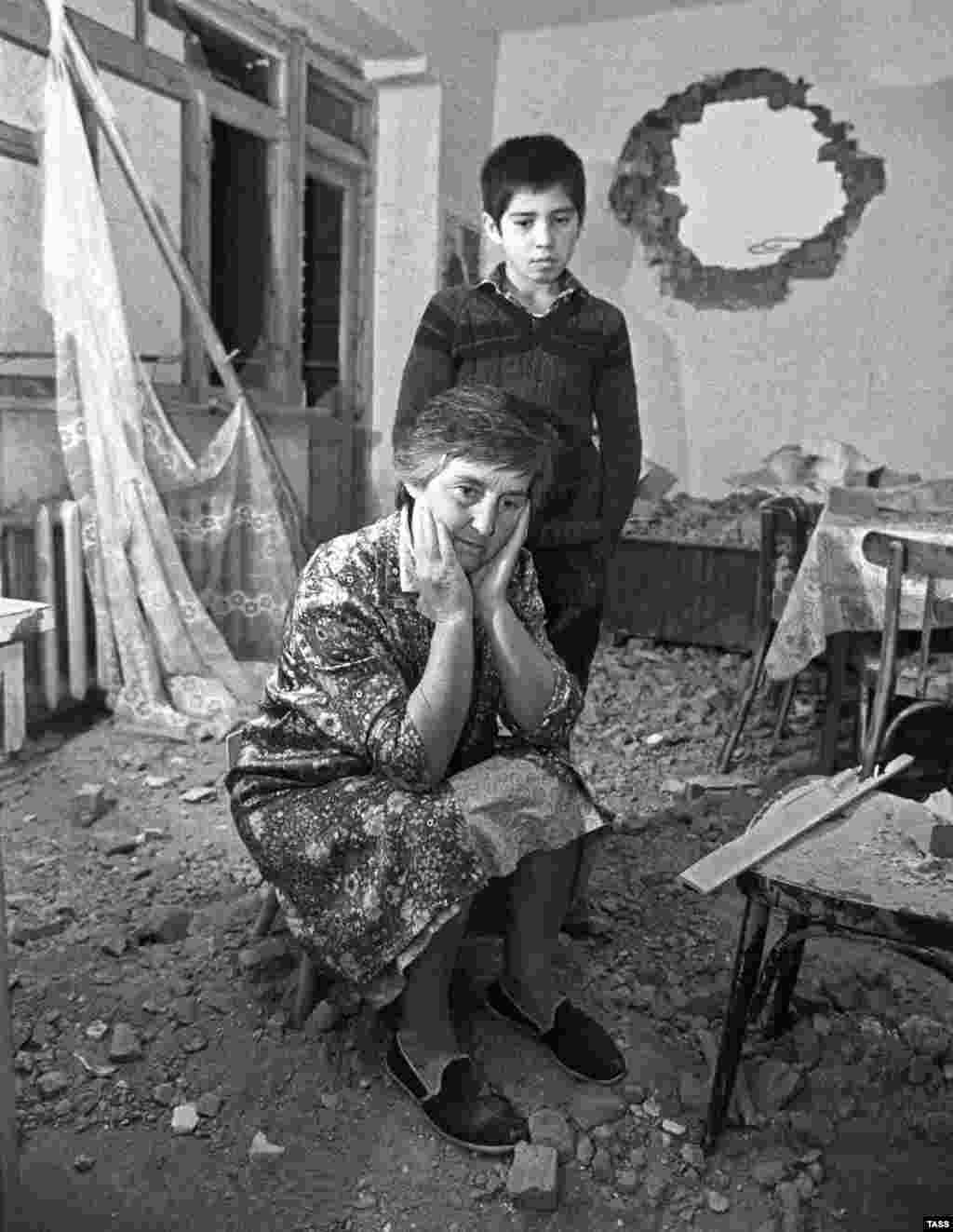 """A woman sits in her apartment that was badly damaged during fighting between ethnic Georgians and Ossetians in 1991.  The war has been called the most """"pointless"""" of Georgia's conflicts that broke out amid the collapse of the Soviet Union, but its consequences still loom large over the Caucasus."""