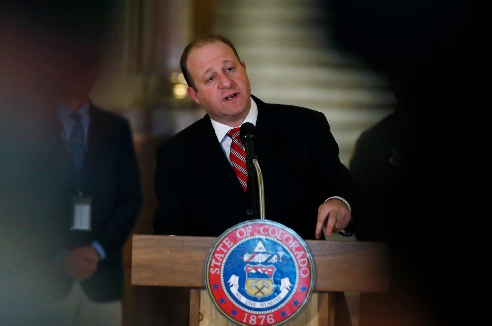 In this Monday, March 16, 2020, photograph, Colorado Gov. Jared Polis makes a point during a news conference about the state's efforts to fend off the spread of coronavirus in the Centennial State. On Monday, March 23, Polis signed a bill to abolish the death penalty and reduce the terms to life in prison for Colorado's three, death-row inmates. (AP Photo/David Zalubowski)