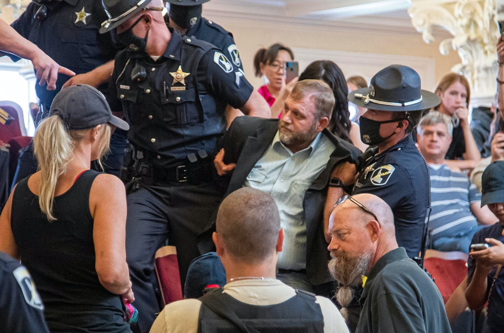 Ammon Bundy is dragged from the Idaho Senate Chambers gallery by Idaho State Troopers after returning to the Idaho Statehouse Wednesday, Aug. 26, 2020 in Boise. Officers cited a statute before taking Bundy into custody a day after being arrested for refusing to leave a committee meeting. (Darin Oswald/Idaho Statesman via AP)