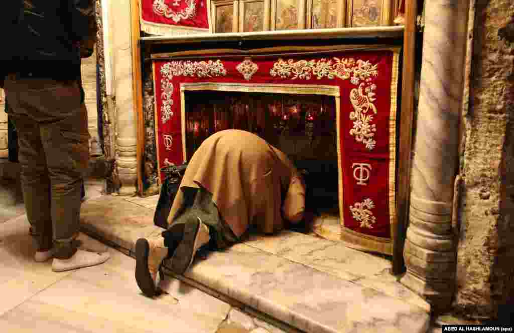 A woman prays in the Church of the Nativity in the West Bank city of Bethlehem. The grotto in the church is considered by Christians to be the birthplace of Jesus Christ.