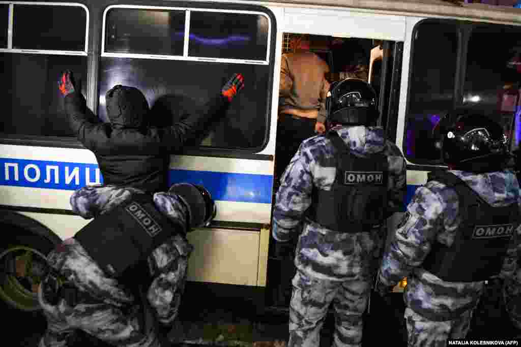 A police officer searches a detainee in downtown Moscow early on February 3.