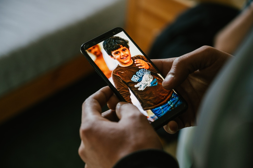 Fady looks at a picture of his brother on his cell phone. He has not seen Mhamad for over 5 years. In the photo, which is his only one, he is 9 years old.