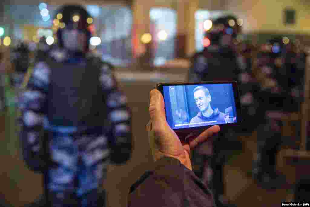 A journalist watches a livestream of the Navalny sentencing hearing as National Guard soldiers stand in front of the court in Moscow. The court converted a years-old suspended sentence to a prison term for a financial-crime conviction widely seen as politically motivated.
