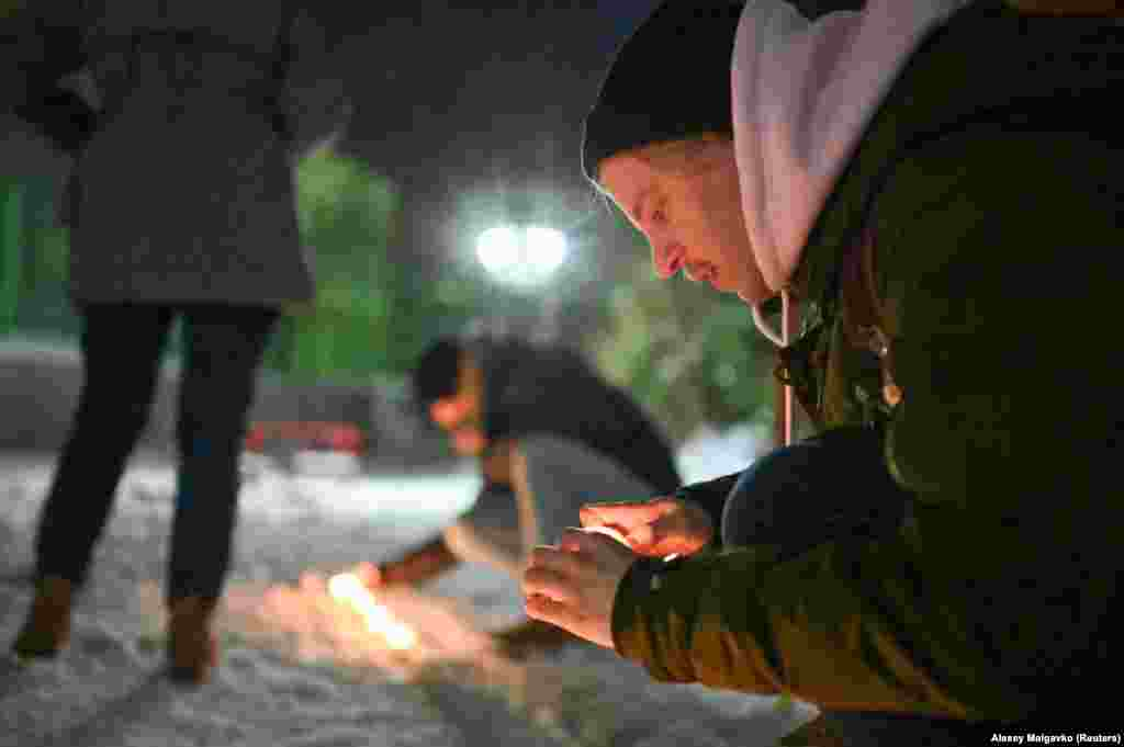 Navalny supporters light candles in a courtyard in Omsk.