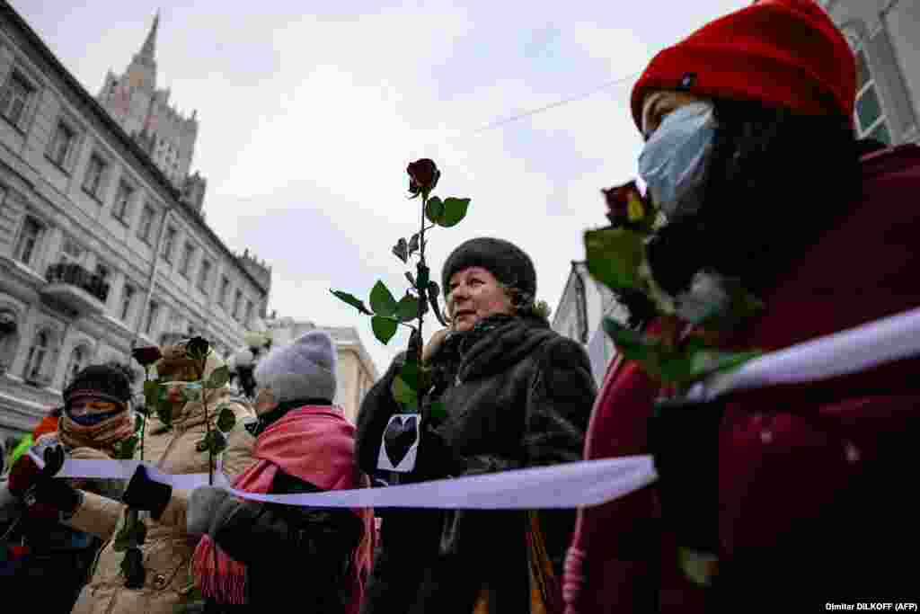 Russian women hold flowers as they form a human chain in Moscow to express support for Navalny on February 14.