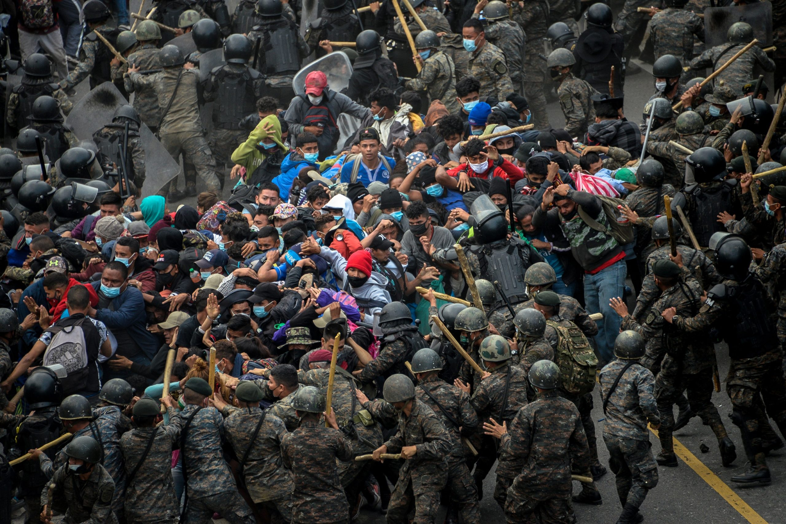TOPSHOT - Honduran migrants, part of a caravan heading to the United States, clash with Guatemalan security forces in Vado Hondo, Guatemala on January 17, 2021. - Guatemalan police fired tear gas Sunday to try to disperse a caravan of thousands of migrants heading toward the United States. (Photo by Johan ORDONEZ / AFP) (Photo by JOHAN ORDONEZ/AFP via Getty Images)