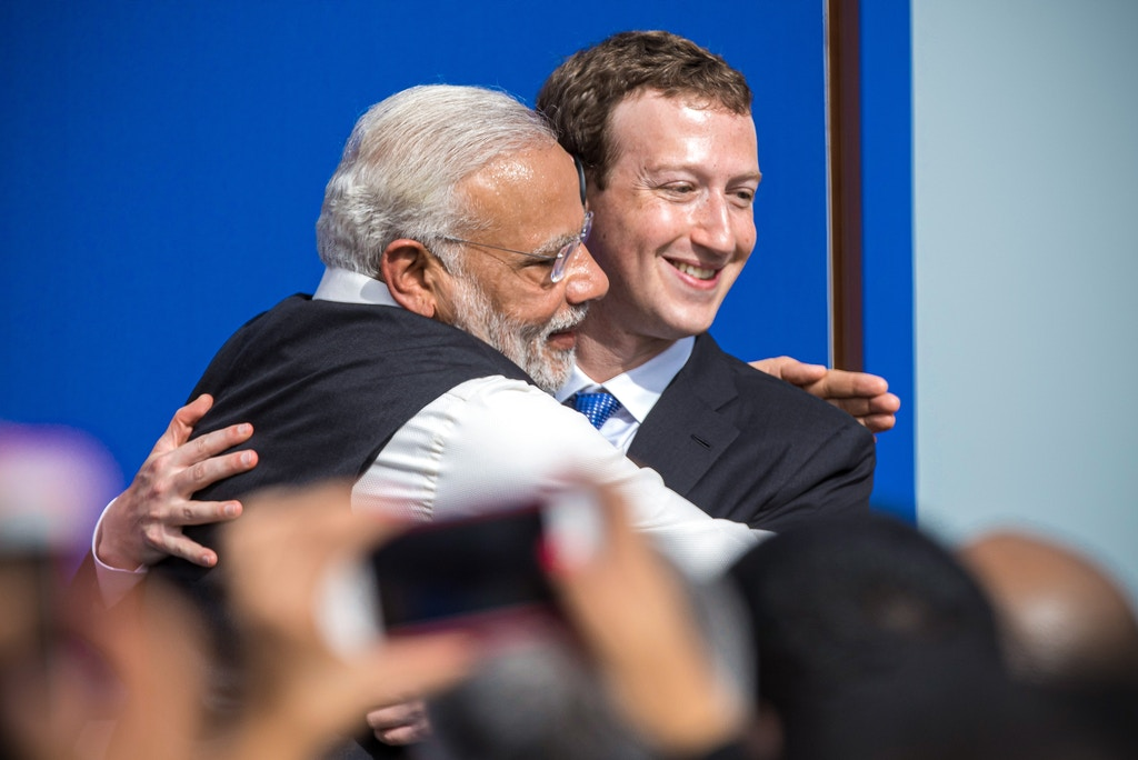 """Narendra Modi, India's prime minister, left, and Mark Zuckerberg, chief executive officer of Facebook Inc., embrace at the conclusion of a town hall meeting at Facebook headquarters in Menlo Park, California, U.S., on Sunday, Sept. 27, 2015. Prime Minister Modi plans on connecting 600,000 villages across India using fiber optic cable as part of his """"dream"""" to expand the world's largest democracy's economy to $20 trillion. Photographer: David Paul Morris/Bloomberg via Getty Images"""