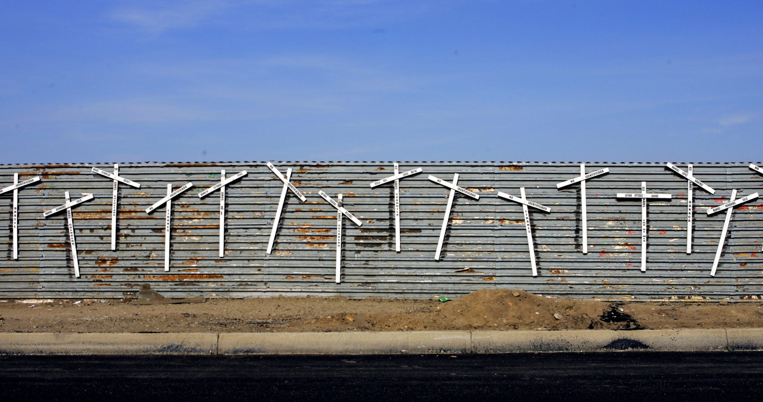 Crosses are posted on the wall that separates the US and Mexico 29 January 2006 in Tijuana, Mexico. According to the US Border Patrol, some 2,000 immigrants have died crossing into the US in the period 1998-2004 as operation Gatekeeper was being developped as a way to secure the border. To avoid such a perilous journey Mexico's National Human Rights commission announced a plan to distribute maps showing safe routes into the US, a move that created indignation by anti-immigrant groups and conservative politicians in the US. Because of this response Mexican officials have declined to implement the plan.  AFP PHOTO/Omar TORRES / AFP / OMAR TORRES        (Photo credit should read OMAR TORRES/AFP via Getty Images)