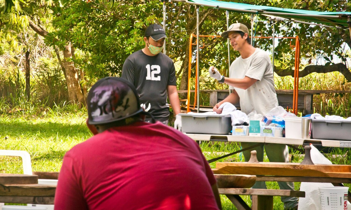 Youth mentor Loa Patao, right, demonstrates how to clean boiled kalo before pounding it to make the Hawaiian food staple poi. (Photo: Malia Welch)