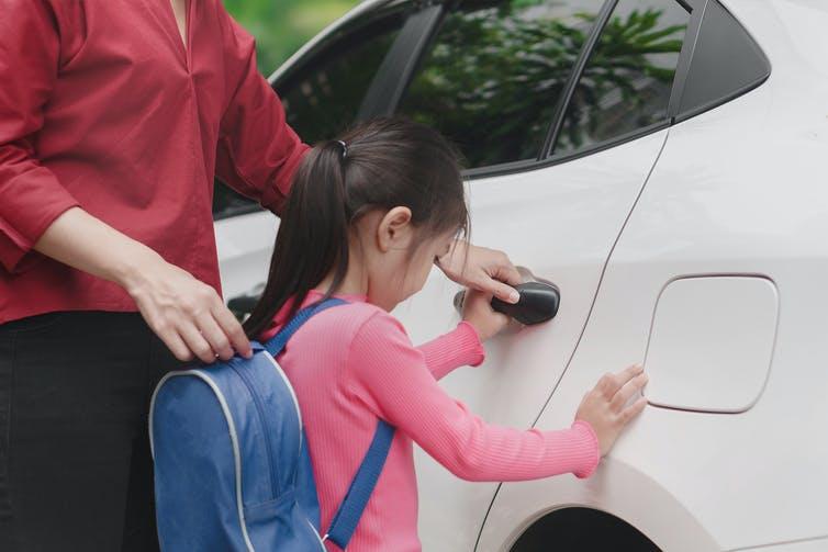 Mother opens car door for girl going home after school