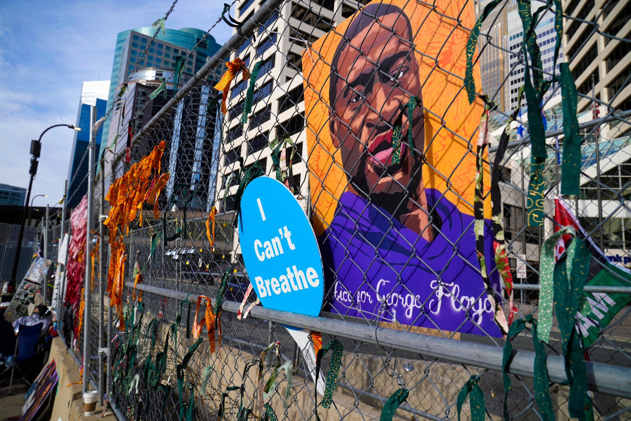 A picture of George Floyd hangs on a fence outside the Hennepin County Government Center, Tuesday, March 30, 2021, in Minneapolis where the trial for former Minneapolis police officer Derek Chauvin continues. Chauvin is charged with murder in the death of Floyd during an arrest last May in Minneapolis. (AP Photo/Jim Mone)
