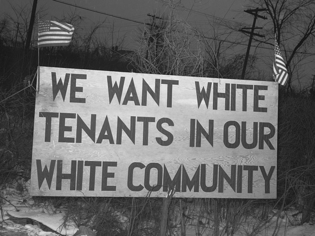 """Detroit, Michigan. Riot at the Sojourner Truth homes, a new U.Sn federal housing project, caused by white neighbors' attempt to prevent Negro tenants from moving in. Sign with American flag """"We want white tenants in our white community,"""" directly opposite the housing project. Source: Library of Congress"""